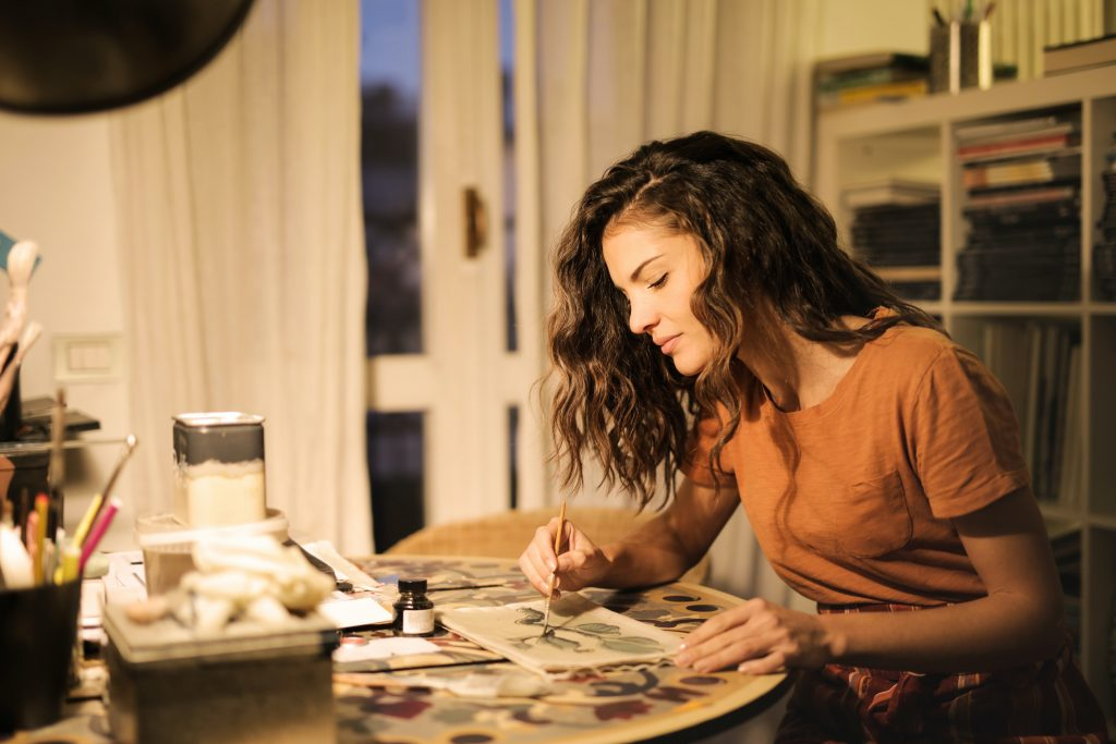 woman sitting at a desk doing creative solutions such as illustration
