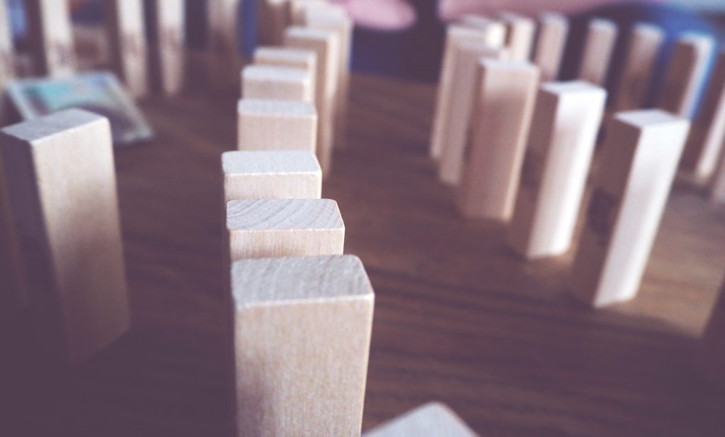 a picture of dominoes stood up ready to fall - representing compounding effect