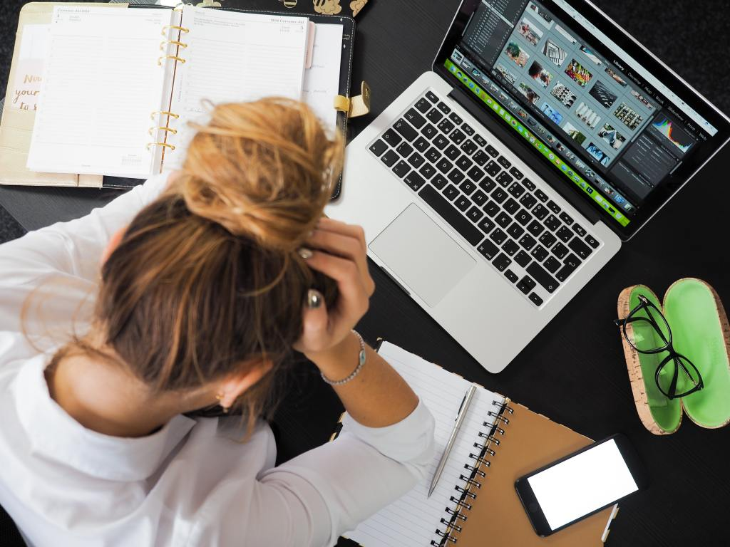 woman at laptop with her head in her hands - critical / destructive thoughts