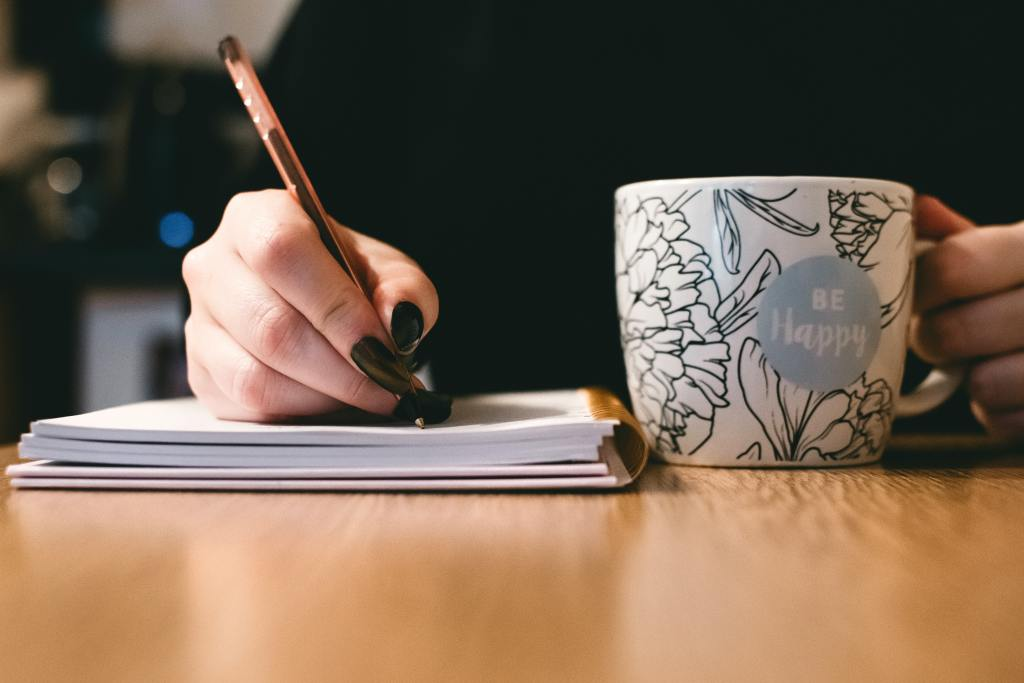 woman with cup of tea, writing down something - writing your bio for LinkedIn