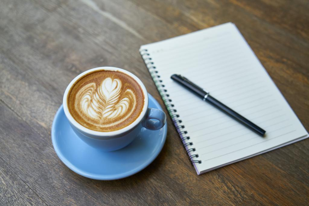 image of a cup of coffee and a notebook - symbolising work life balance and working holistically
