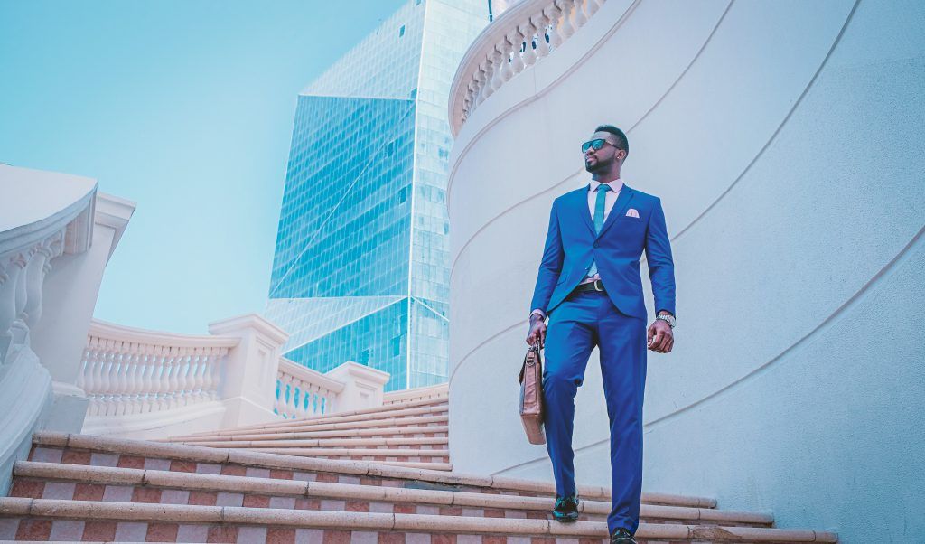 """image of a male in a suit walking down a flight of stairs holding a briefcase, personifying the stereotypical """"entrepreneur"""" who doesn't do apprenticeships"""