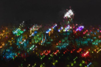 Electric city buildings come alive at night. A painted look has given unintentional camera movement a vibrant abstract impression of the scene.