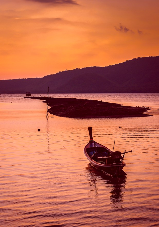 As day is dawning a long boat waits to go to work in Chalong Bay, Phuket