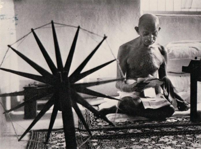गांधी चरखे पर सूत कातते हुए।