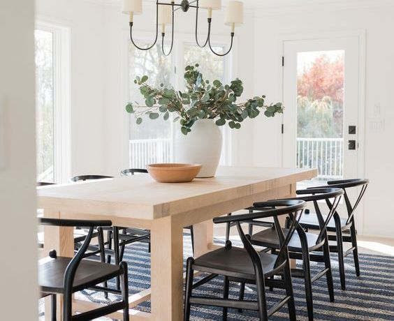 Beautiful dining room with striped rug and black wishbone side chairs