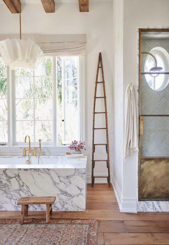 Beautiful modern bathroom with marble tub surround - Amber Interiors - Tessa Neustadt