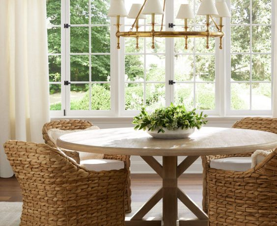 Beautiful dining room with light wood round dining table, woven dining chairs and brass chandelier with lampshades