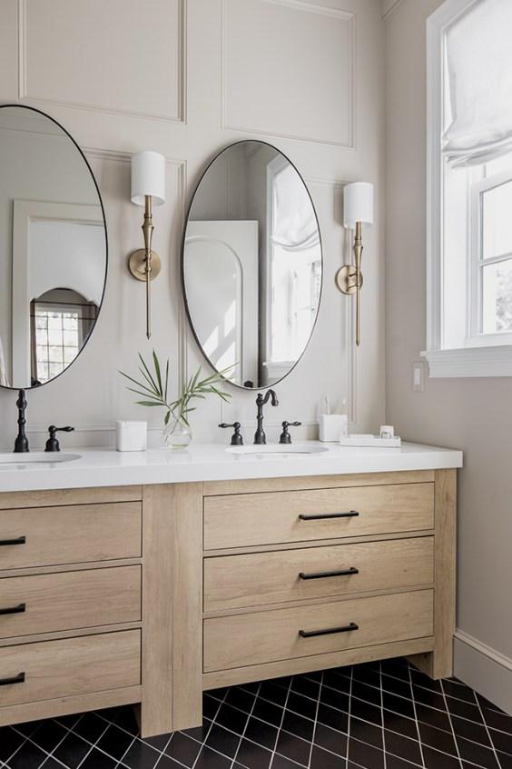 Beautiful bathroom with light wood vanity, black hardware, brass sconces and round mirrors - Jenna Sue Design