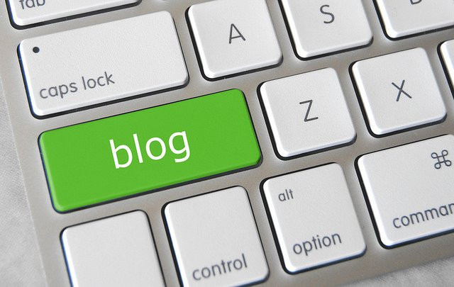 """A white keyboard with a green """"blog"""" key"""