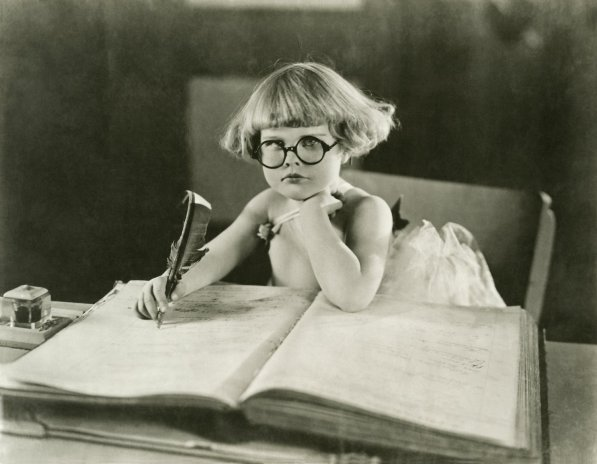 A young child wearing round glasses and writing in a large ledger with a quill pen