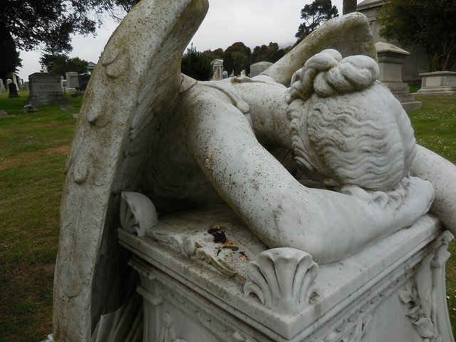 A stone angel resting her head on a plinth in apparent grief