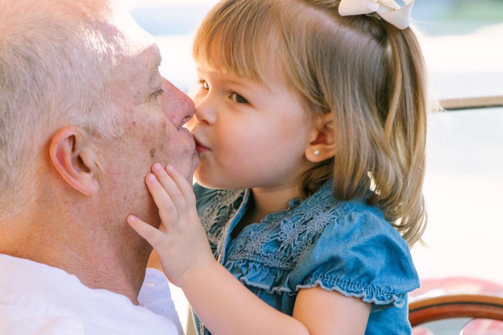 Granddaughter kissing grandpa