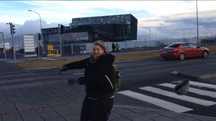 Hat blowing off in front of the Harpa, Iceland