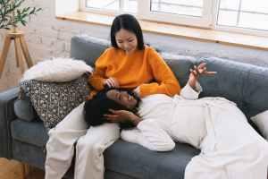 happy black pregnant woman lying on legs of asian female