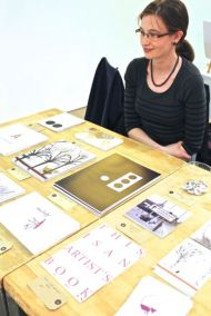 Laura Little and some of her Pink Parrot Press books and cards.
