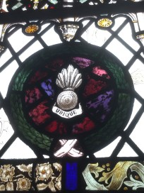 Detail of stained glass window showing regimental motif or badge.