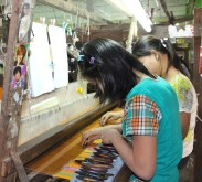 Weaving silk by hand -- note the photos of movie stars.