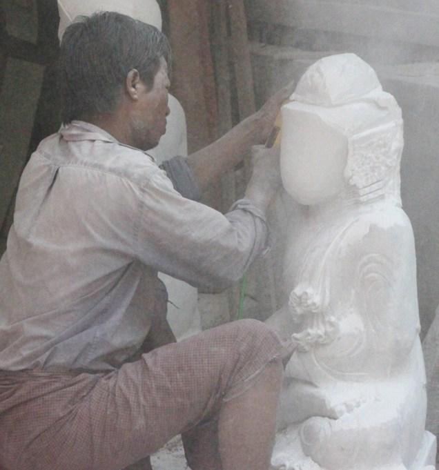 Carving a stone Buddha.