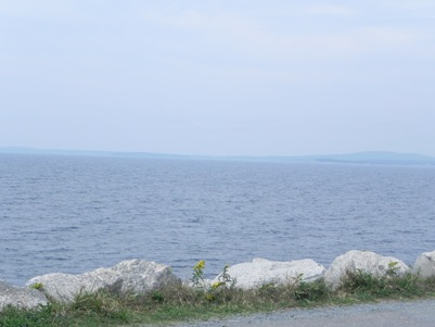 View from the bench: plenty of ocean, with the rock-lined edge of a roadway in the foreground.