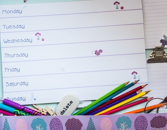 Weekly planner with coloured pencils, pens, eraser and stickers.