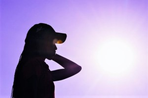 silhouette of woman in baseball cap against purple background