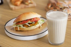 sandwich on bun with glass of milk