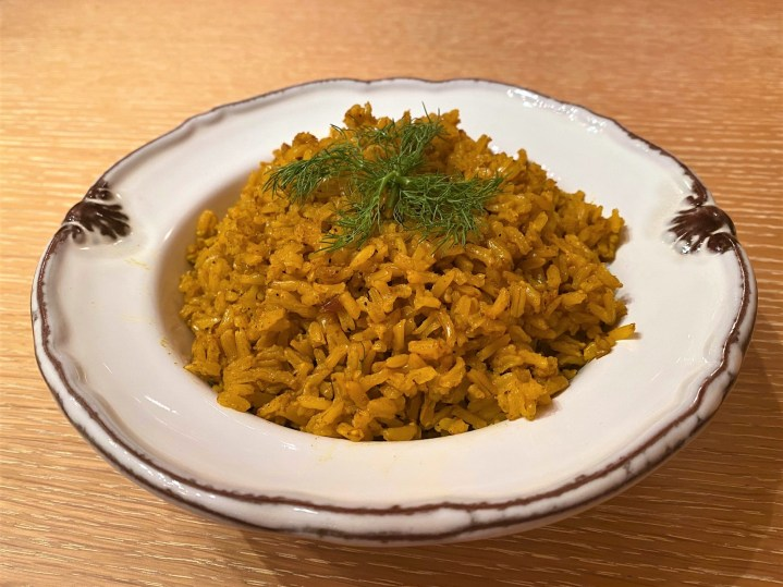 Spice-infused golden turmeric rice in white serving bowl