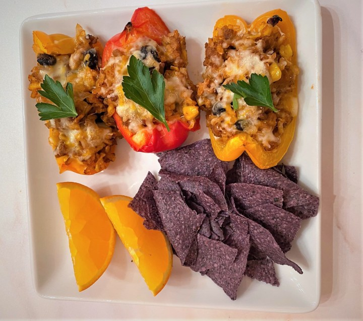 Taco Stuffed Peppers on white plate with blue corn tortilla chips and orange slices