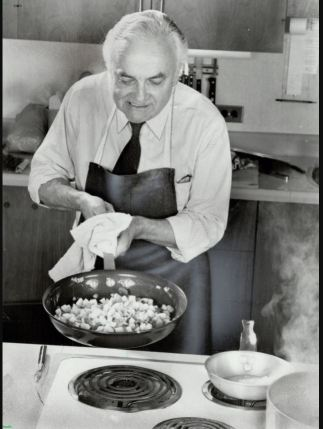 Black and white photo of Pierre Franey cooking with a large frying pan