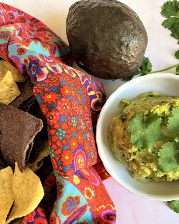 macamole (guacamole) with basket of blue and white tortilla chips, fresh cilantro and avocado