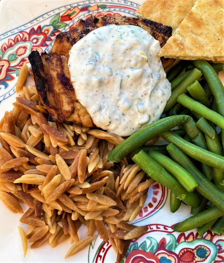 dinner of grilled chicken with yogurt sauce, orzo, green beans and naan