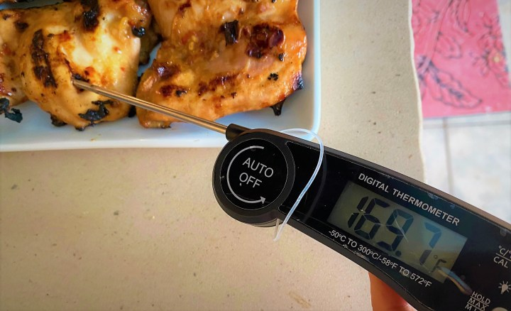 digital thermometer inserted in chicken thigh with grill marks