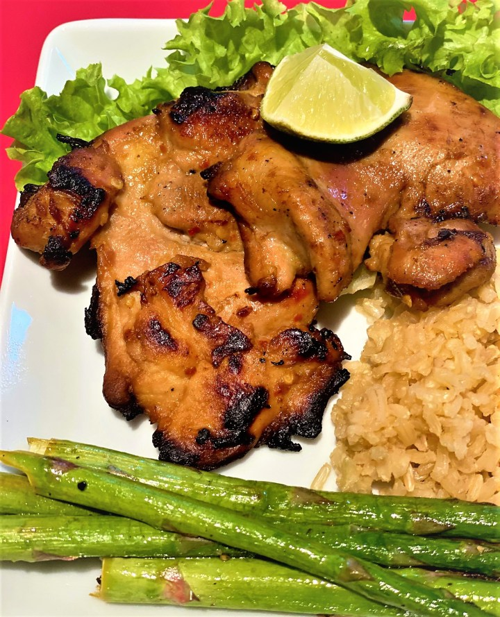 grilled boneless chicken thighs with a lime wedge, brown rice and asparagus
