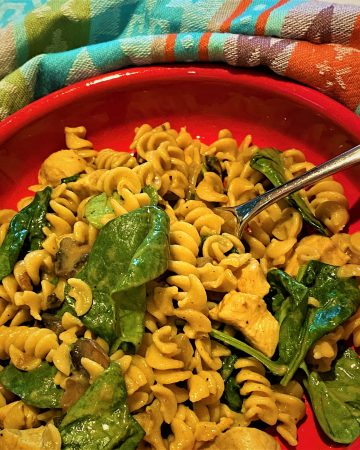 Creamy, curried, chickpea rotini with spinach and mushrooms in a red dish with a colorful kitchen towel
