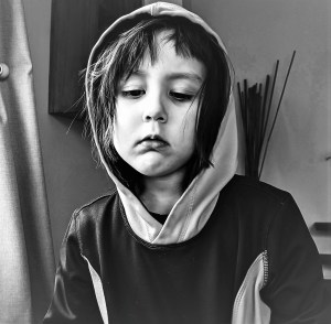 black and white photo of sad looking child in a hood