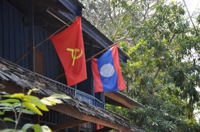 """""""Kolor czerwony symbolizuje krew rozlaną w walce o niepodległość, niebieski bogactwo kraju. Białe koło oznacza księżyc widziany nad rzeką Mekong oraz jedność kraju pod komunistycznym rządem.""""."""
