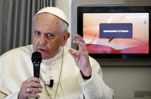 Pope Francis gestures as he answers questions from a journalist during the flight from Colombo, Sri Lanka, to Manila in the Philippines January 15, 2015. CREDIT: REUTERS/ STEFANO RELLANDINI
