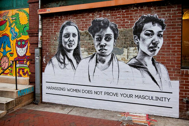 """This photo shows a large-scale poster on a brick wall, featuring the faces and upper torsos of three women, with the words underneath: """"Harassing women does not prove your masculinity."""" The artwork is by Tatyana Fazlalizadeh."""