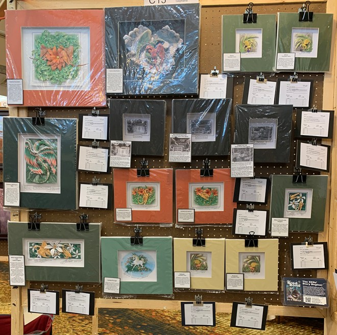This photo shows an Art Show display panel at SpikeCon absolutely crammed with 15 matted paper sculptures by Jan S. Gephardt.