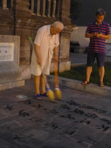 北京の路上で習字する人