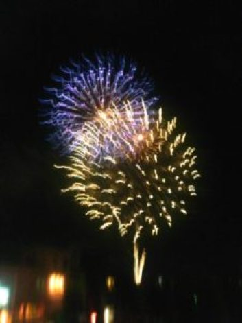two fireworks explode at different heights