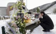 Un père prie sur le mémorial de l'école où allait son fils disparu le 11 mars.