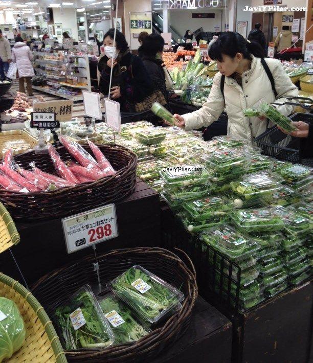 Mujer comprando un paquete de siete hierbas para nanakusagayu (七草粥) el 6 de enero en un supermercado de Kobe (Japón)
