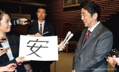 Shinzo Abe recibiendo el Kanji del Año 2015, que aparece también en su apellido