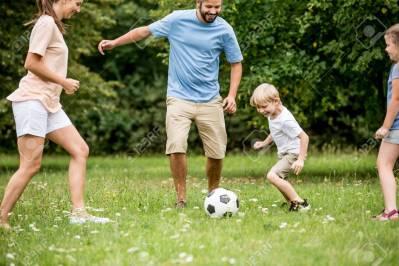 87069565-garçon-et-famille-jouant-au-football-et-s-amuser-au-jardin-min