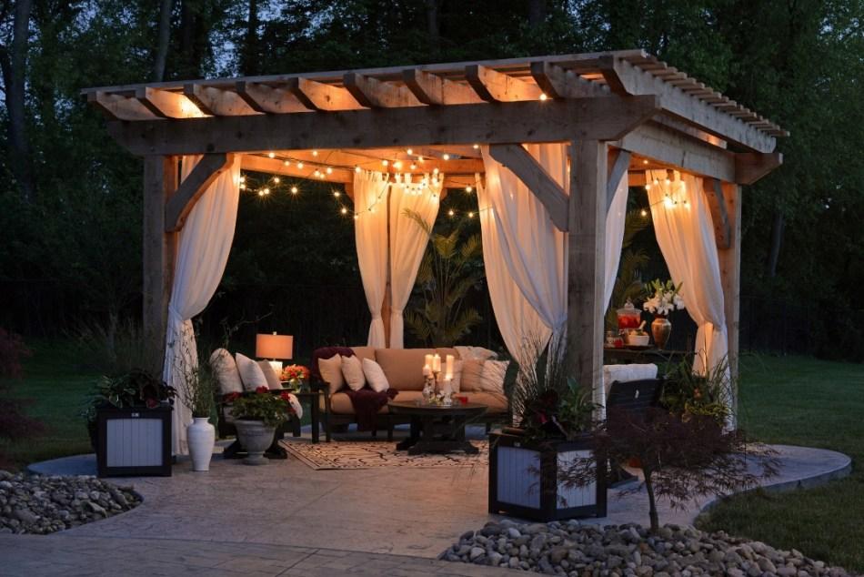 Espace extérieur polyvalent avec kiosque de jardin, éclairage et sièges confortables.