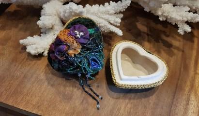 Boîte en terre cuite sertie de tissu brodé de perles et de pompons en satin, INDE - Prix de vente : 15€.