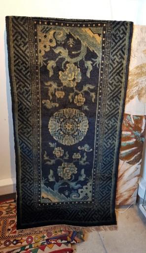 """Tapis """"Pao Tao"""" en laine ; à médaillon central décoré de fleurs sur fond bleu, tissage traditionnel fait à la main avec jute (Fin 19ème siècle), CHINE - Dimension : 121 cm x 57 cm - Prix de vente : 690€."""