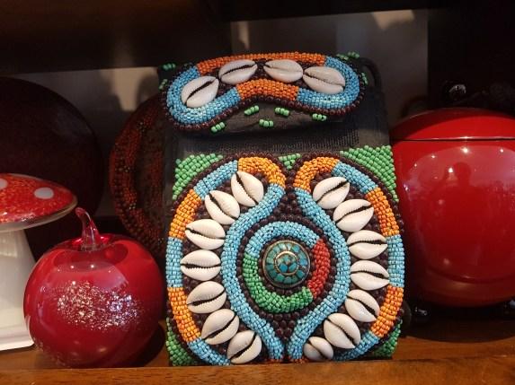 Pochette en coton brodée de cauris et de perles, médaillon en turquoise, anse longue et fermeture en velcro, NEPAL – Prix de vente : 60€.
